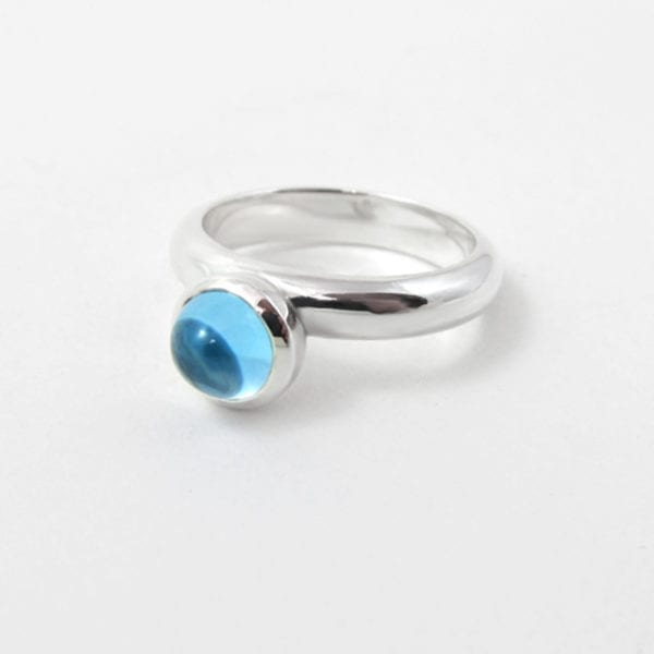 Blue topaz cabochon ring featuring a domed birthstone
