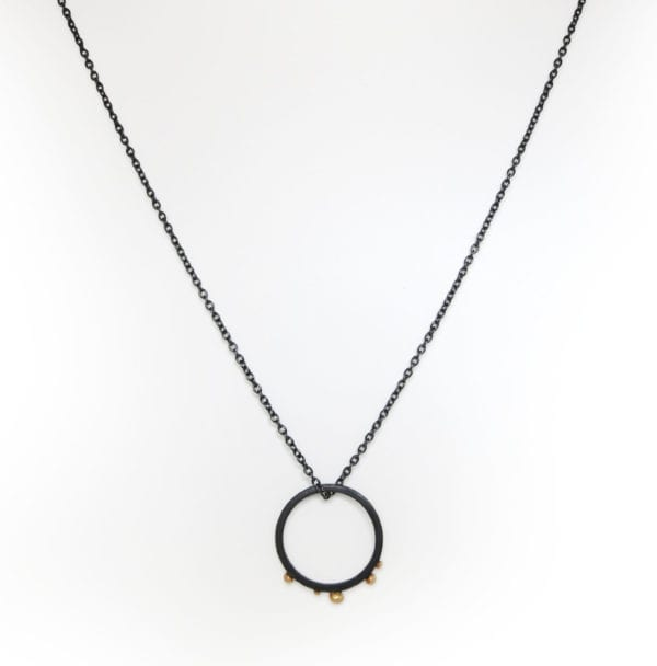 Black circle necklace with gold balls on black silver chain